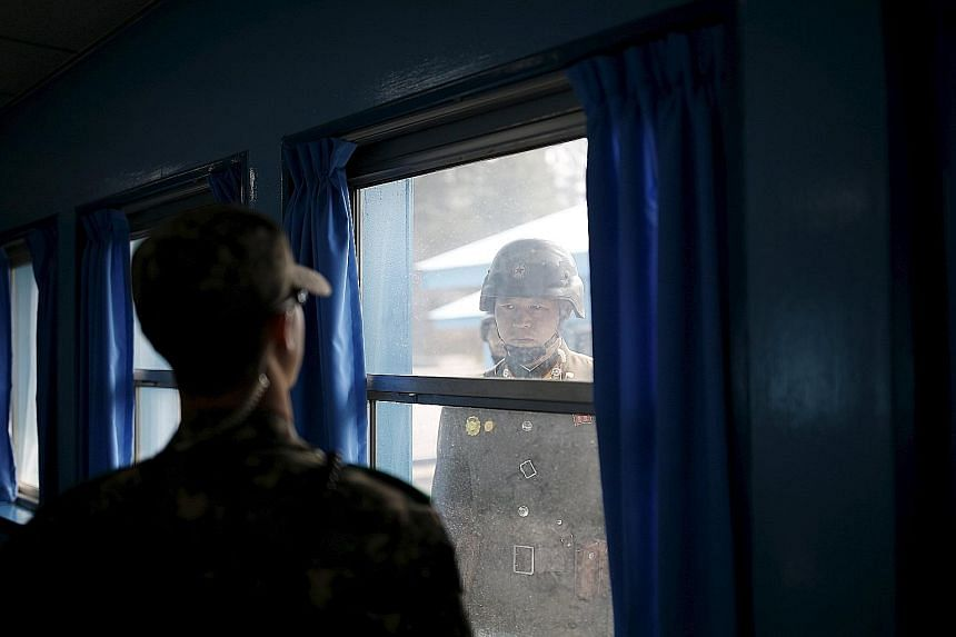 North and South Korean soldiers eyeballing each other at the truce village of Panmunjom yesterday. The two sides are technically still at war since their 1950-53 conflict ended in an armistice, not a peace treaty.