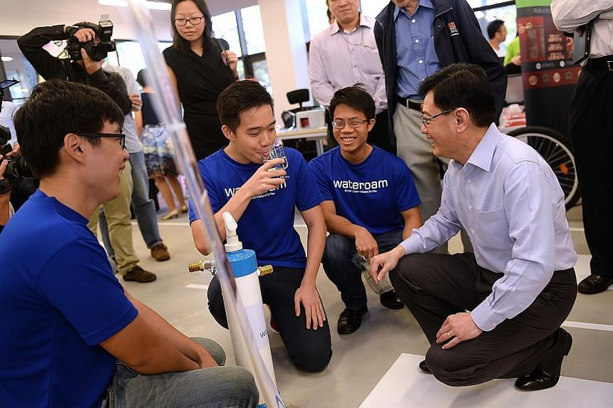 Mr Heng (at right) watching as Mr Lim Chong Tee, 24, chief marketing officer of start-up WateROAM, takes a sip of water from the company's Fieldtrate Plus, a water filter hand pump.