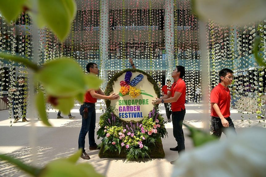 Workers putting the finishing touches to the the world's largest floral chandelier, made from more than 60,000 flowers, which set a Guinness World Record.