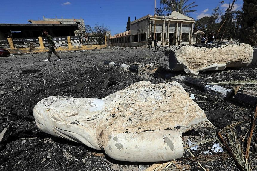 The remains of a statue in a debris-strewn street in the ancient city of Palmyra on Thursday. The city was recaptured by government troops on Sunday. Mr Assad (below) said he would consider ending his current seven-year term early if that was what Sy