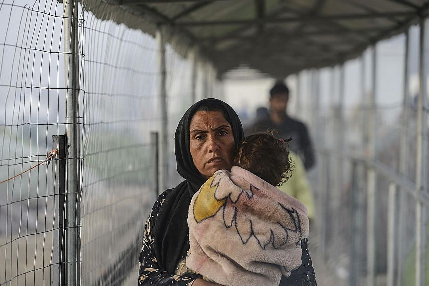 A migrant woman and child at a makeshift camp on the Greek-Macedonian border yesterday. Turkey says migrant returns from Greece to Turkey will start on Monday under its deal with the EU.