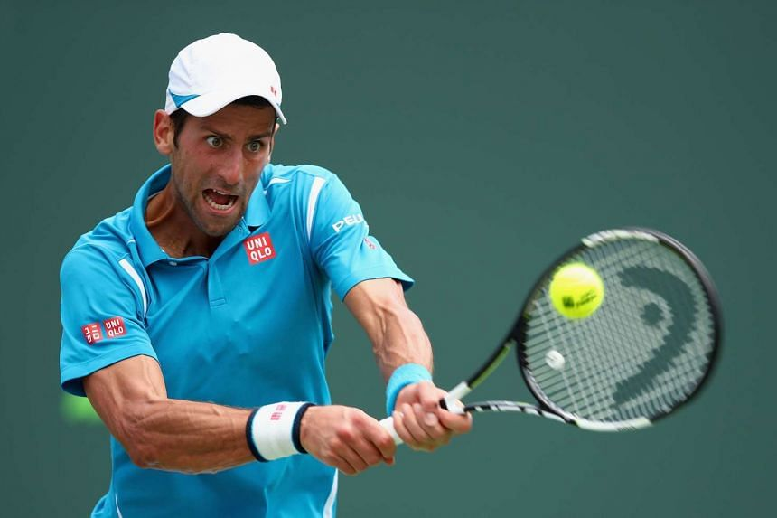 Djokovic of Serbia plays a backhand against David Goffin.