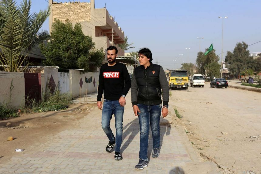 Murtada Hamid (left), 26, and his brother Mustafa, 29, who both came back to Iraq after spending time in Germany, walking on a street in the Iraqi town of Aziziyah, on Feb 21.