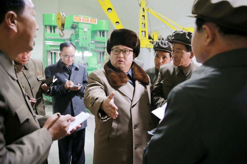 North Korean leader Kim Jong Un (centre) tours a factory in an undated photo released April 1, 2016.