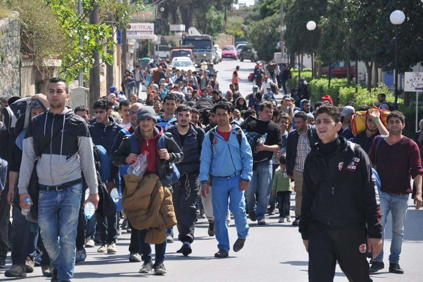 Migrants walk in a street of Chios city, on Chios island, Greece, April 1, 2016.