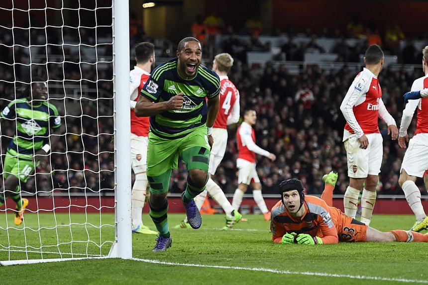 Arsenal's players are stunned as Swansea City's Ashley Williams (left) scores the winner against them in a Premier League clash on March 2. The Gunners took the lead but allowed their bottom-half rivals to bounce back and win 2-1.