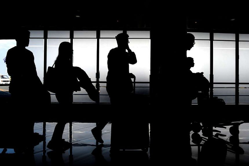 Passengers queuing up as they arrive at the departures area at Manila's international airport on March 23, 2016. A power outage plunged a major section of the Philippine capital's main airport into darkness overnight, forcing flight cancellations tha