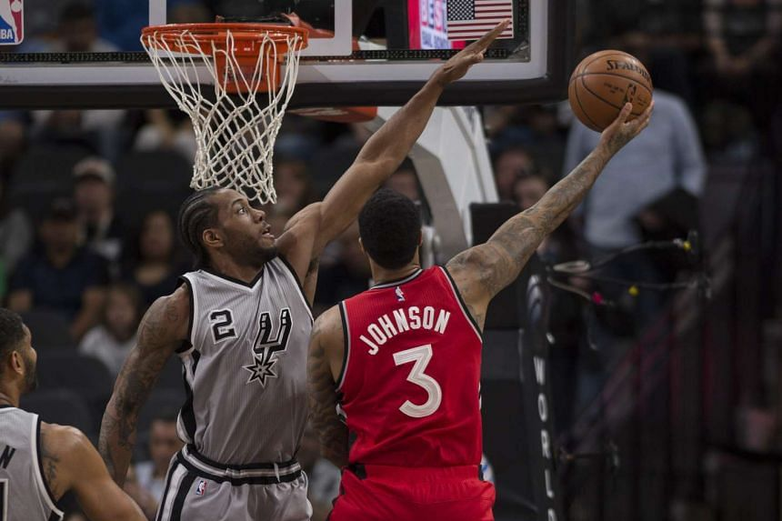 San Antonio Spurs forward Kawhi Leonard (left) defends against Toronto Raptors forward James Johnson during the first quarter at the AT&T Center.