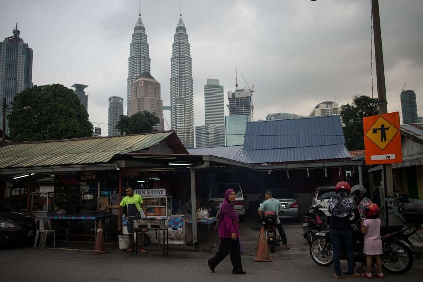 A woman walking past a restaurant as Malaysia's iconic Petronas Twin Towers loom in the background in Kampung Baru.