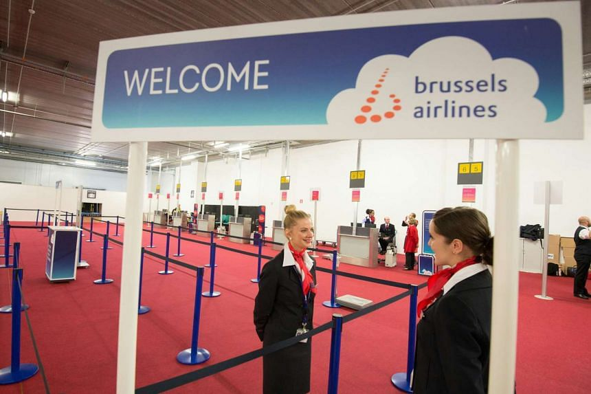 Brussels airline employees wait for passengers at a temporary check-in area at Brussels airport on its reopening day on April 3, 2016.