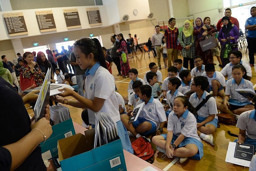 PSLE inspires a certain madness among parents, who snap up assessment books during their children's PSLE year. Pupils receiving their PSLE results. The revamped system will use letter grades instead of an aggregate score.