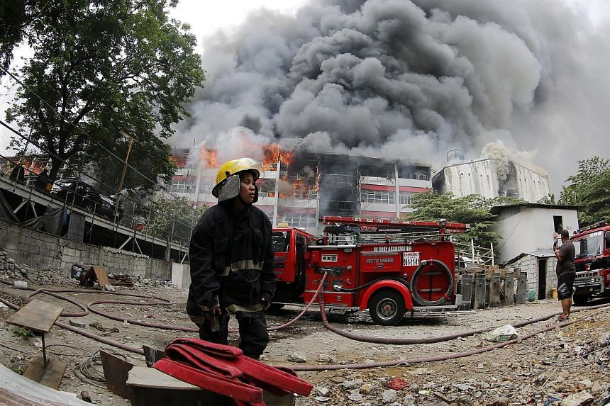 A firefighter at the scene of a massive blaze at the University of the East campus in Manila yesterday. Media reports say welding work at the College of Arts and Sciences building may have sparked the fire, which spread to two other buildings. Studen