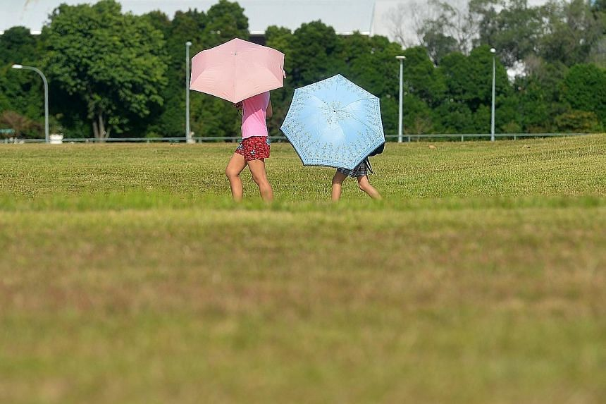 People carrying umbrellas to shield themselves from the blazing sun in Bishan central yesterday. Singapore experienced its hottest day this year when the temperature soared to a blistering 35.6 deg C yesterday. The weatherman has cautioned that tempe