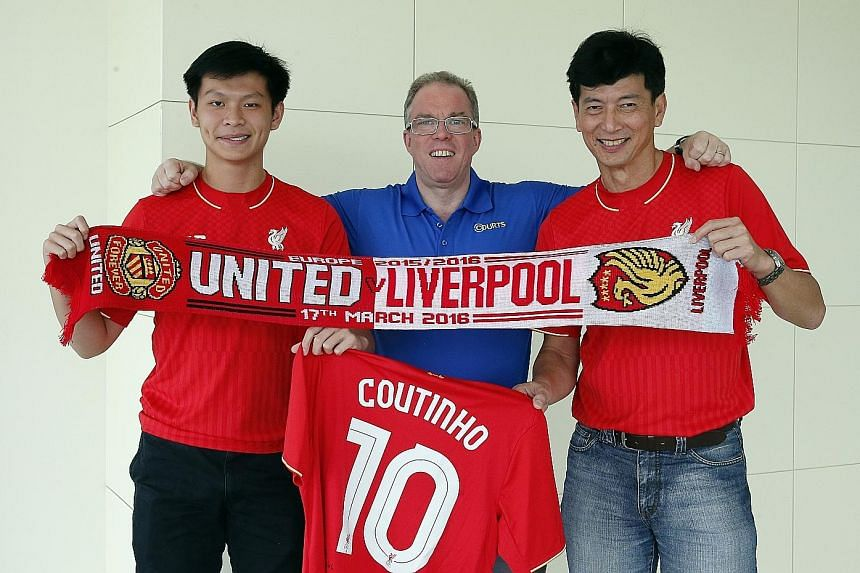 Ashley (left) and Vincent Ong flank Courts CEO Terry O' Connor. The father and son display the Manchester United-Liverpool Europa League match scarf and the signed jersey they received from their favourite player Philippe Coutinho.