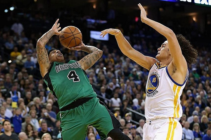 Isaiah Thomas of the Boston Celtics (left) finds plenty of air time as he goes up for a shot against Anderson Varejao of the Golden State Warriors in the 109-106 victory at Oracle Arena on Friday.