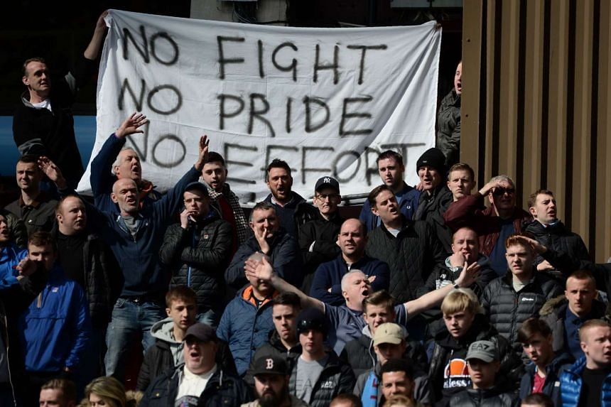 Aston Villa fans hold a sign criticising their team.