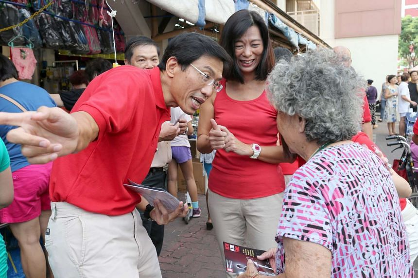 SDP's Chee Soon Juan and his wife Huang Chih-Mei speaking to an elderly resident during his party's walkabout.