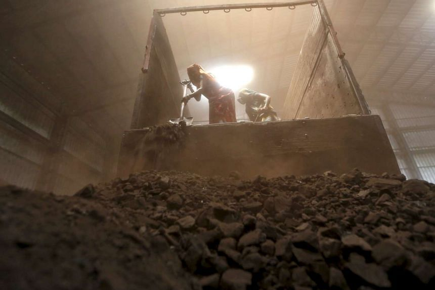 Workers unload coal from a supply truck at a yard on the outskirts of the western city of Ahmedabad, India.
