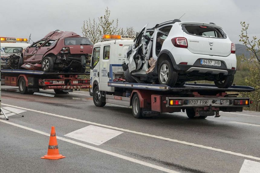 Two tow trucks carrying damaged vehicles wait on the motorway near Figueras on April 2, 2016, following the crash.