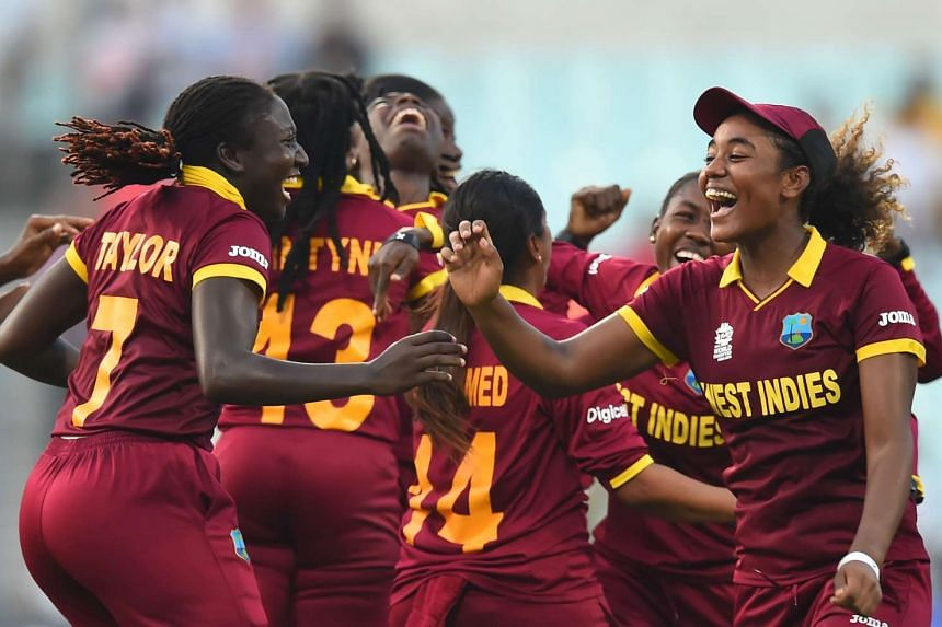 West Indies's Stafanie Taylor (left) with Hayley Matthews (right) and teammates celebrate their victory in the World T20 cricket tournament women's final match at The Eden Gardens Cricket Stadium in Kolkata.