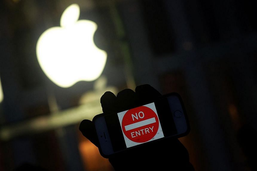 """This file photograph hows an anti-government protester holding his iPhone with a sign """"No Entry"""" during a demonstration near the Apple store on Fifth Avenue in New Yor"""