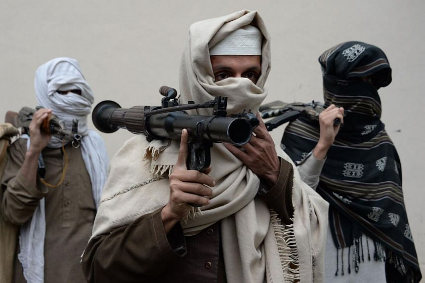 Former Afghan Taleban fighters carry their weapons before handing them over as part of a government peace and reconciliation process in Jalalabad, on Jan 12, 2016.