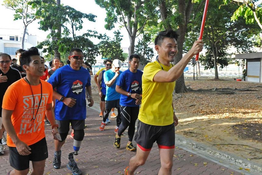 """Parliamentary Secretary for the Ministry of Culture, Community and Youth, Mr Baey Yam Keng, running alongside Singapore's """"Blade Runner"""", Shariff Abdullah Peters (second from left), and participants."""