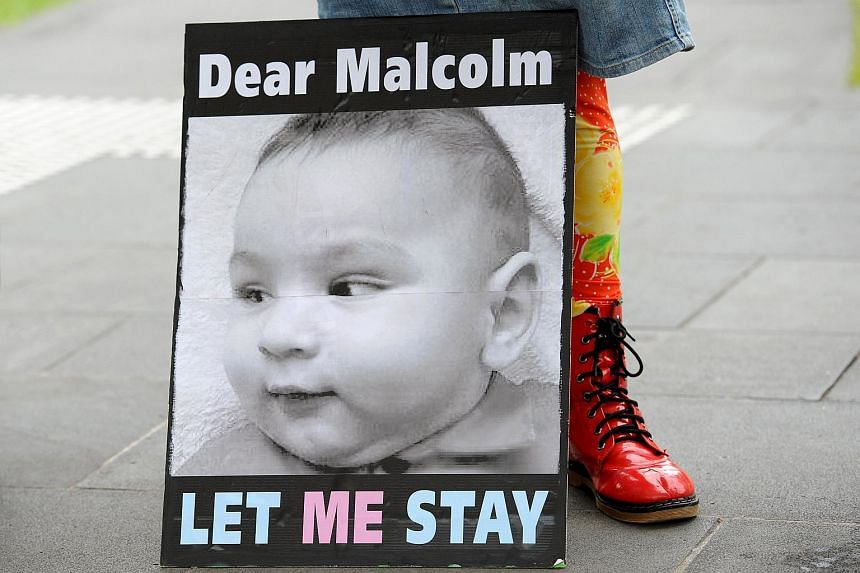 A banner calling for Australian Prime Minister Malcolm Turnbull to allow the infant children of asylum seekers to remain in Australia is shown during a demonstration in Melbourne.