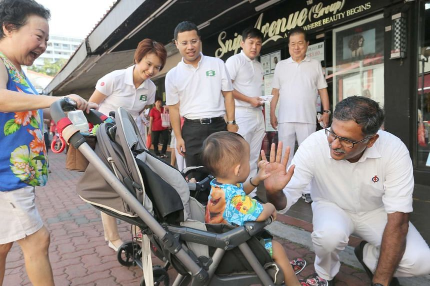 Mr Murali high-fiving a young boy in a pram during his walkabout.