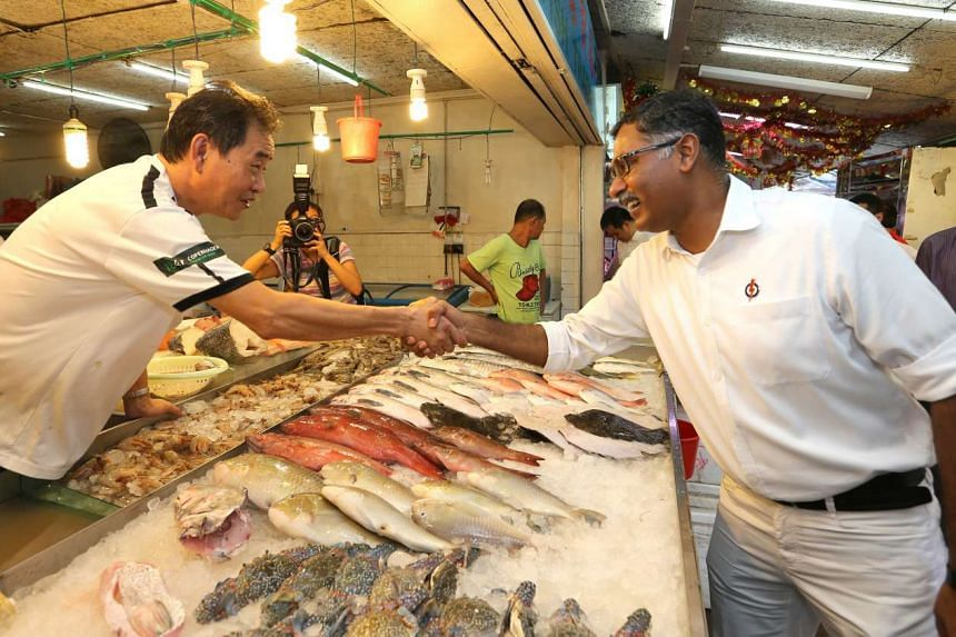 Mr Murali shaking hands with a fishmonger during his walkabout in the market.