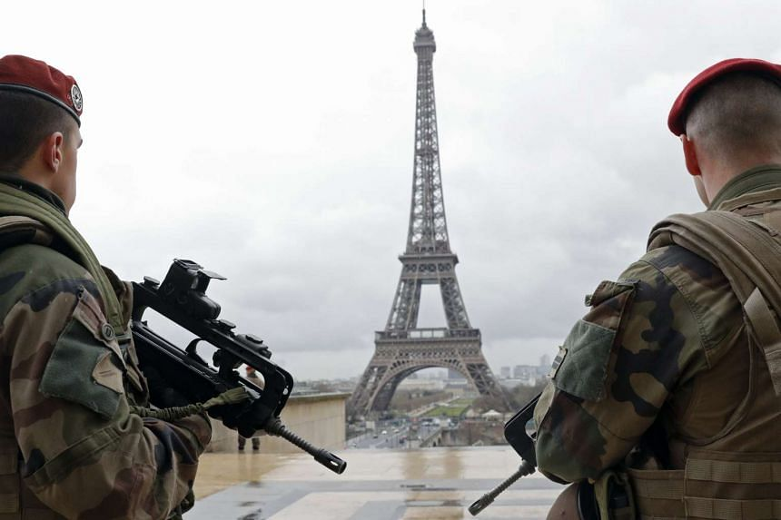 French army paratroopers patrol near the Eiffel tower in Paris, France, March 30, 2016.
