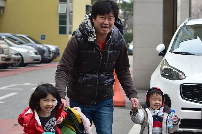 South Korean father Kim Jin Sung taking his daughter Na Eun and son Won Woo home from a childcare centre in Seoul. Fathers in South Korea get five days of paternity leave, but less than 2 per cent take it up. Those who are on paternity leave have to