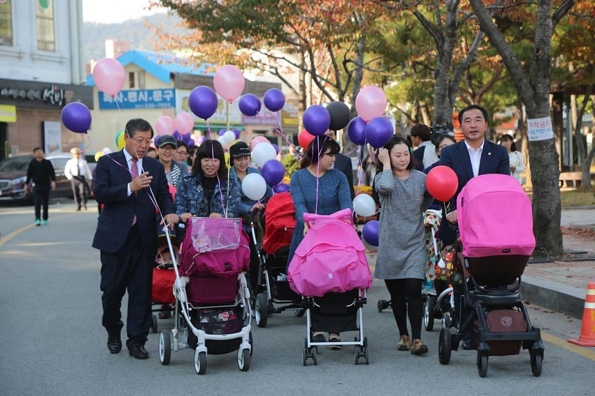 Haenam county mayor Park Cheol Hwan (in suit) with a group of 300 mothers and their babies in a march through Haenam's main street last November to celebrate the county's high fertility rate of 2.4.