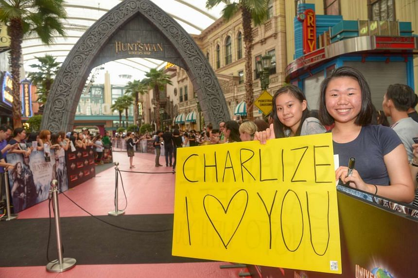 """Students Costance Thum (left) and Choo Tong Lin, both 16, holding up a handmade """"Charlize I Love You"""" placard."""
