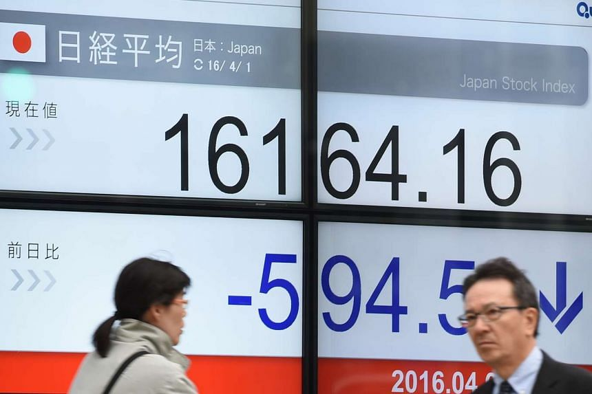 People walk past a quotation board flashing the Nikkei key index of the Tokyo Stock Exchange (TSE) in Tokyo on April 1, 2016.