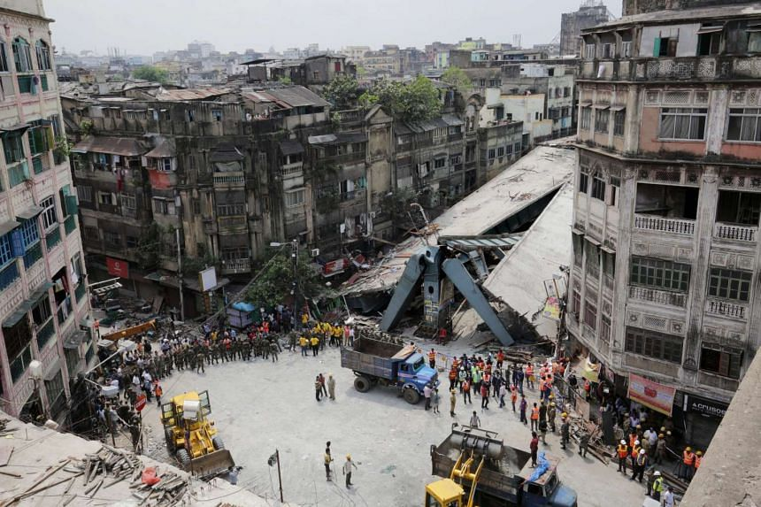 National Disaster Response Force and Indian army personnel handle rubble after a bridge under construction collapsed in Calcutta, India, on April 1, 2016.