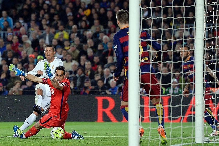 Real Madrid's Cristiano Ronaldo finishes past Barcelona goalkeeper Claudio Bravo and Gerard Pique on the line to score the game's winner and his 29th La Liga goal to lead this season's standings.