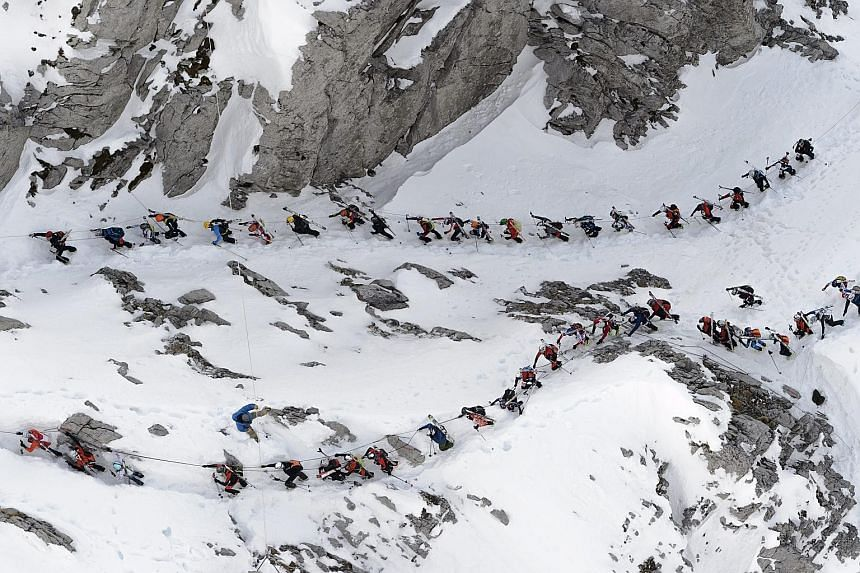 A group of skiers climbing the Col du Pacheu during the 69th edition of the Trophees du Muveran, a ski mountaineering race through the Swiss Alps, above Les Plans-sur-Bex, in Switzerland, yesterday. One of the oldest ski mountaineering races in the w