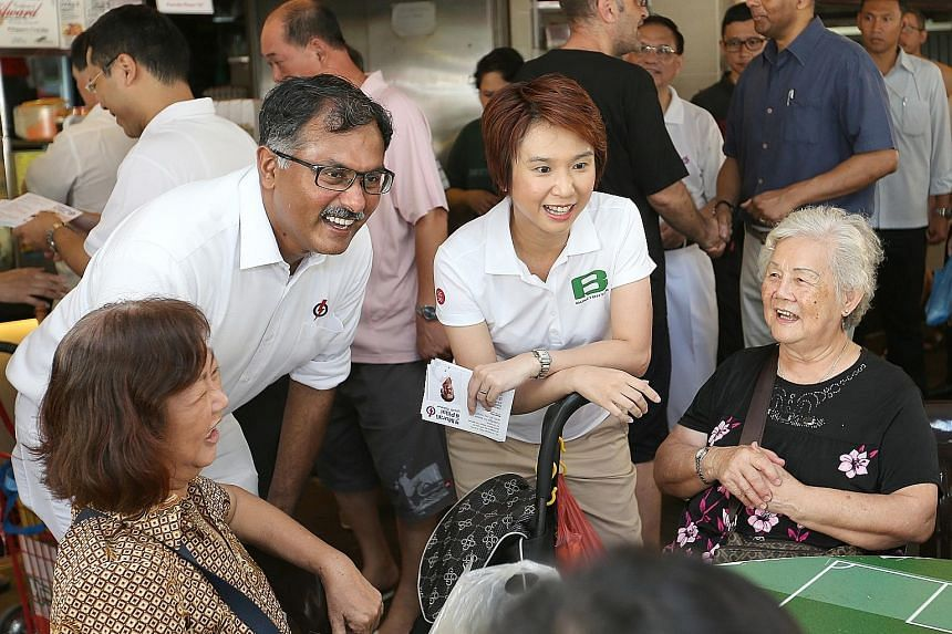 SDP's Dr Chee meeting residents at a coffee shop in the constituency yesterday. Among the party supporters who accompanied him on the walkabout was his sister, Siok Chin (left, behind the photographer). PAP's Mr Murali and Ms Low chatting with reside