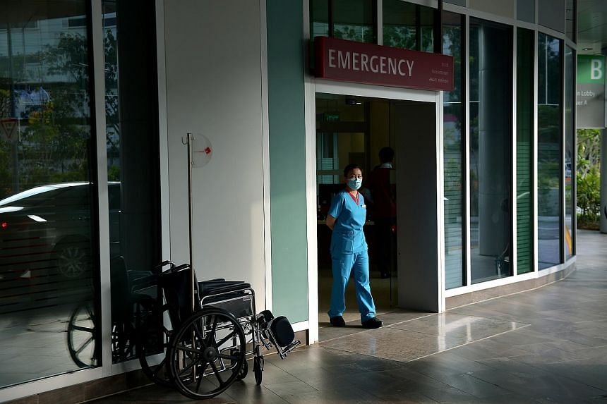 A hospital staff waits at the entrance of the Accident and Emergency Department of Ng Teng Fong Hospital.