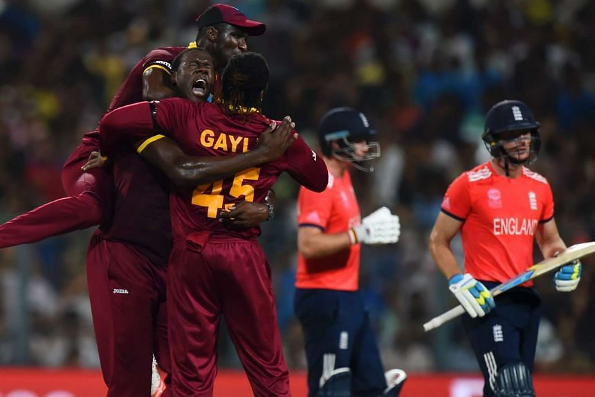 West Indies' Carlos Brathwaite (left)celebrates with teammates Darren Sammy (top) and Chris Gayle(centre) after the wicket of England's Jos Buttler(right).