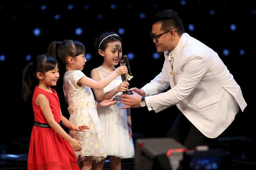 Hong Kong actor Michael Ning receives a trophy from young actresses after winning the Best New Performer award for his role in Port of Call at the Hong Kong Film Awards.