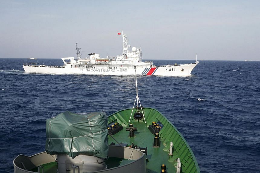 A Chinese Coast Guard ship (top) is seen near a Vietnam Marine Guard ship in the South China Sea, in this May 14, 2010 file photo.