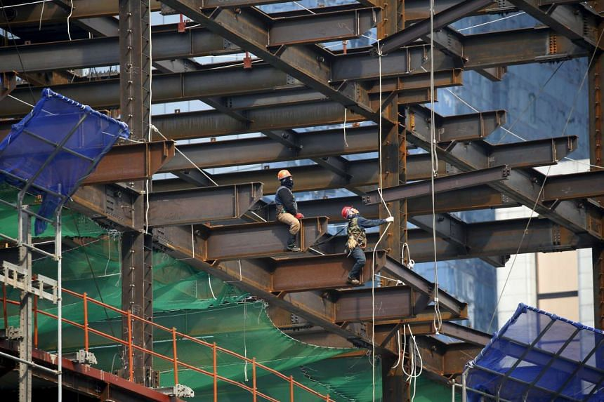 Workers labour on a steel frame at a construction site in central Seoul, South Korea, on March 25, 2016.