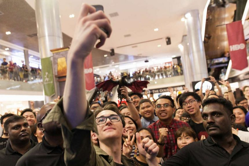English actor Isaac Hempstead Wright (above) taking wefie with fans at the interactive event at Ion Orchard and sitting on the life-sized replica of the iconic Iron Throne.