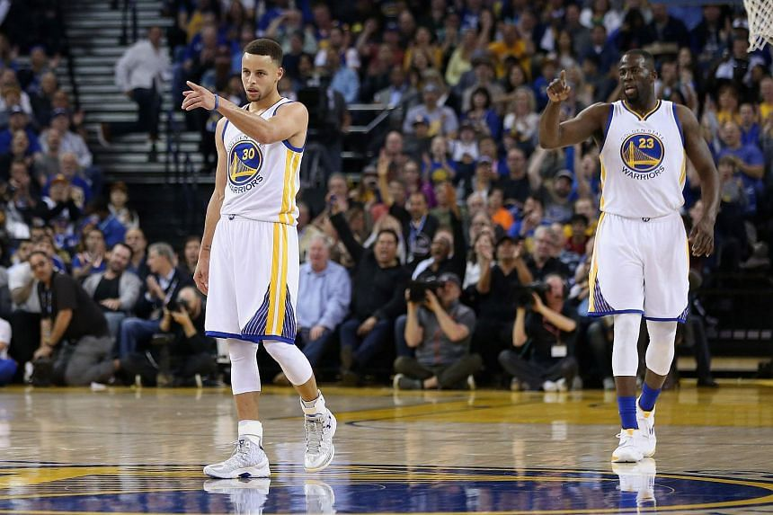 Stephen Curry and Draymond Green of the Golden State Warriors reacting after the Warriors made a basket against the Boston Celtics at Oracle Arena on April 1, 2016.
