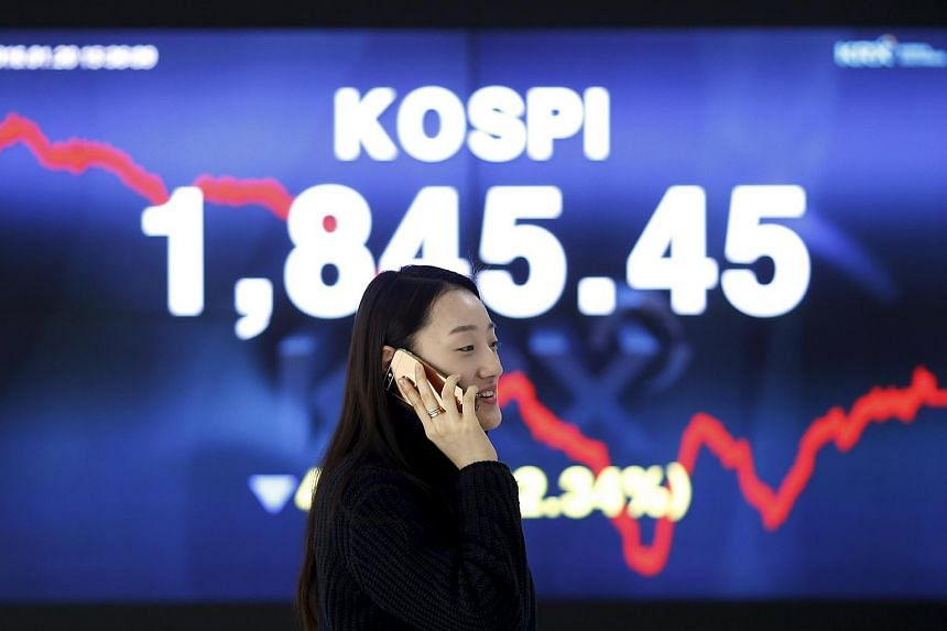 A woman walking past an electronic board of the Korea Composite Stock Price Index at the Korea Exchange in Seoul, South Korea on Jan 20, 2016.