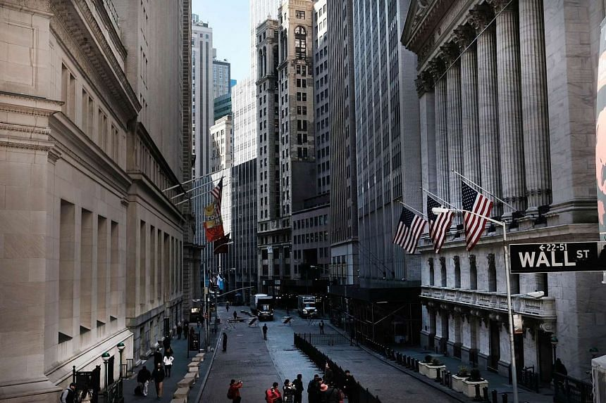 People walk by the New York Stock Exchange (NYSE) near Wall Street on March 21, 2016 in New York City.