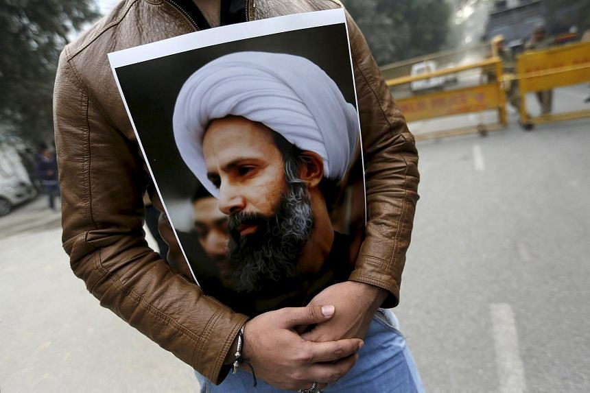 A Shi'ite Muslim man holds a picture of cleric Sheikh Nimr al-Nimr during a protest against the execution of Nimr.