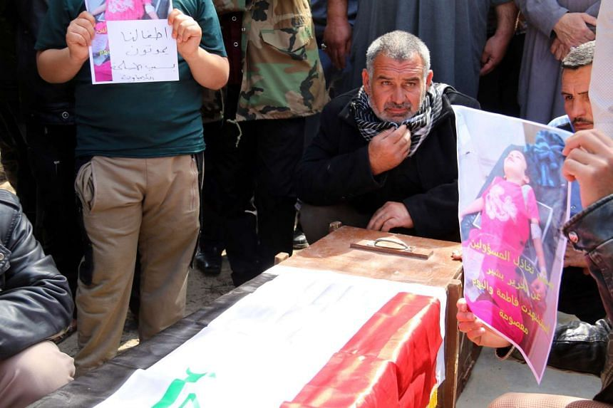 Iraqis mourn over the casket of Fatima Samir, a girl who died of wounds suffered from a suspected mustard gas attack on Taza, around 220 kilometres north of the capital Baghdad, on March 19, 2016.